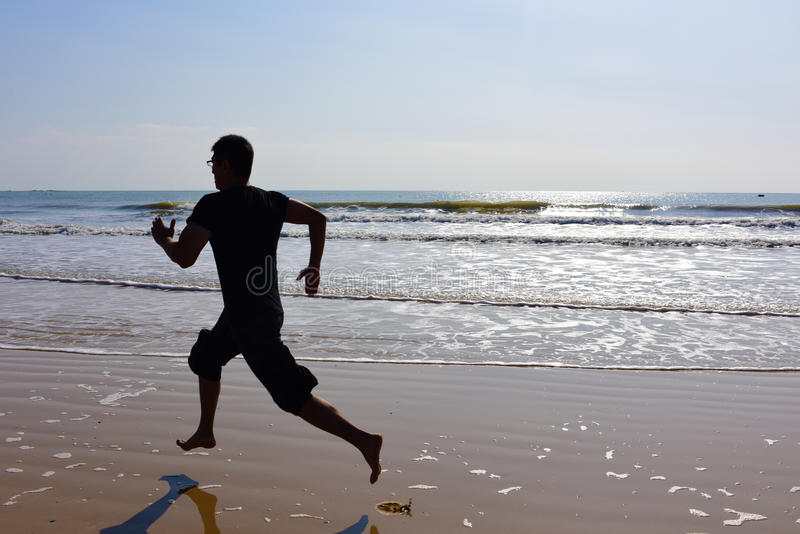 Los pies desnudos sirven el funcionamiento en la playa con las ondas y la reflexión imagenes de archivo