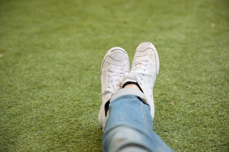 Los pies en zapatillas de deporte se sientan en hierba imagen de archivo