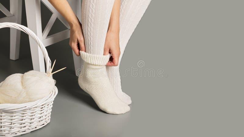 Los pies femeninos en blanco hicieron punto medias y calcetines cerca de la cesta imagenes de archivo