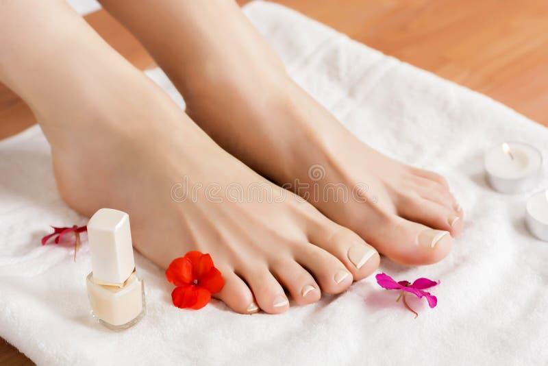 Los pies femeninos hermosos con el francés clavan pedicura en la toalla blanca con las flores y las velas fotografía de archivo