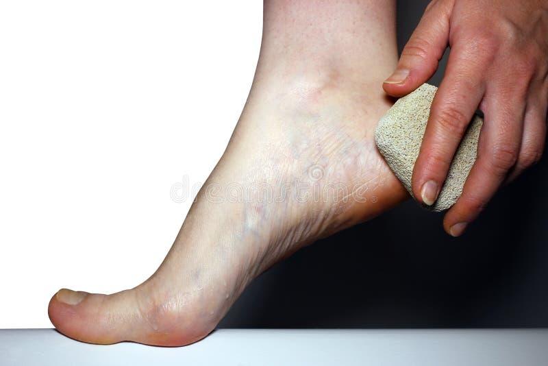 Los pies femeninos se inclinan la piedra pómez de piedra en el aislamiento blanco del fondo, higiene del cuerpo de la forma de vi fotografía de archivo libre de regalías