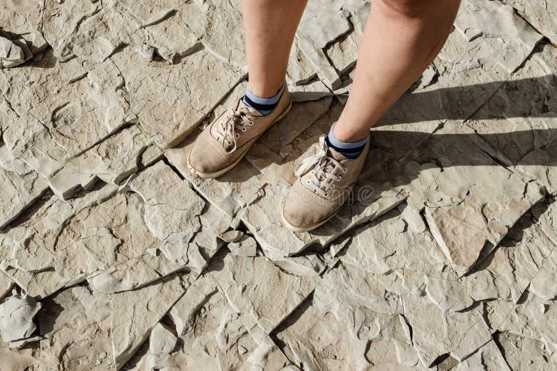 Los pies femeninos y masculinos en calzados informales se están colocando en las losas de piedra naturales Ir de excursión concep imagenes de archivo