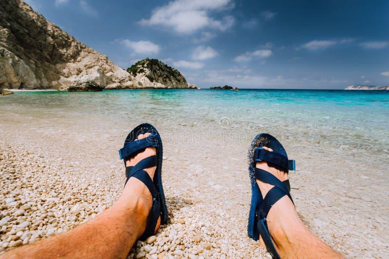 Los pies masculinos jovenes llevan la sandalia azul del balanceo que toma el sol en la playa del mar con agua clara imagenes de archivo