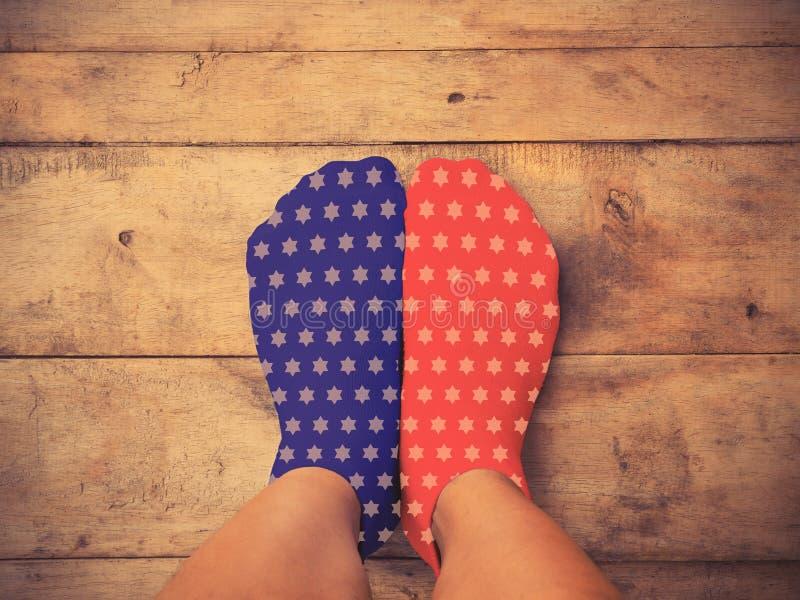 Los pies que llevan calcetines azules y rojos con la estrella blanca forman en de madera imagen de archivo