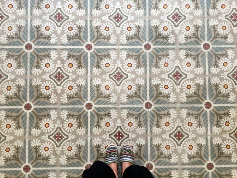 Los pies sobre vintage tejaron el piso imagen de archivo