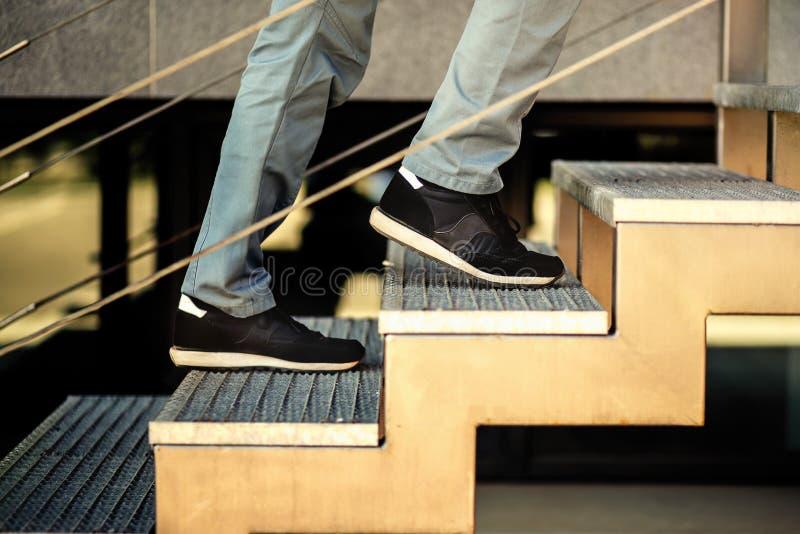 Los pies van encima de las escaleras fotografía de archivo