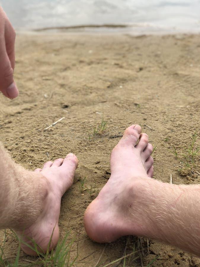 Los pies y la mano de los hombres contra la arena y el río fotografía de archivo