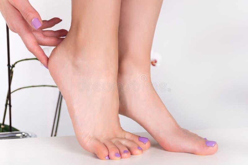 Los pies y las manos de la mujer con los clavos de la lila pulen color fotos de archivo libres de regalías