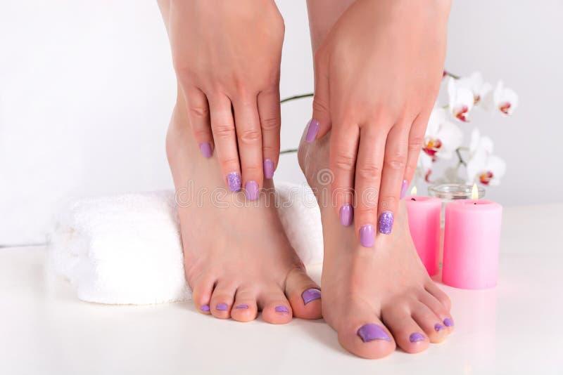 Los pies y las manos de la mujer con los clavos de la lila pulen color imagen de archivo
