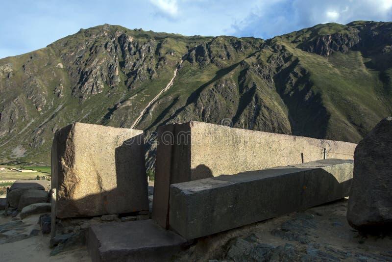 Los pilares de piedra gigantes se sientan encima de Temple Hill en el pico de las ruinas de Ollantaytambo en Perú fotografía de archivo