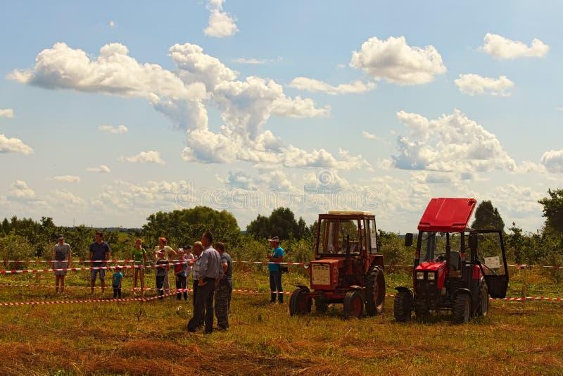 Los pilotos del tractor miran su raza rival Figure la competencia de pilotaje en el campo imagenes de archivo