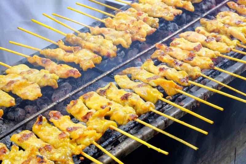 Los pinchos del cerdo asaron a la parrilla en una estufa, cerdo satay son uno de comida de la calle en Bangkok, Tailandia imagenes de archivo