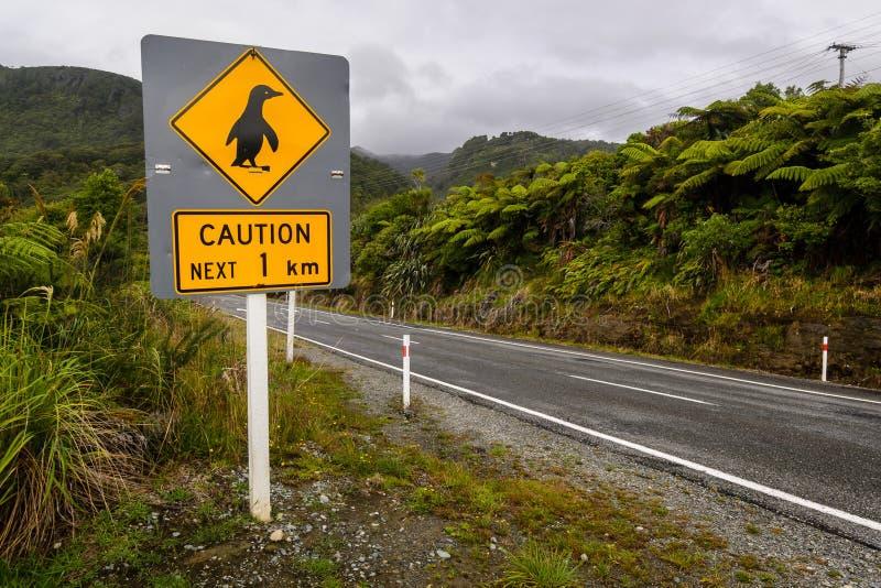 Los pingüinos de la precaución firman adentro NZ fotos de archivo