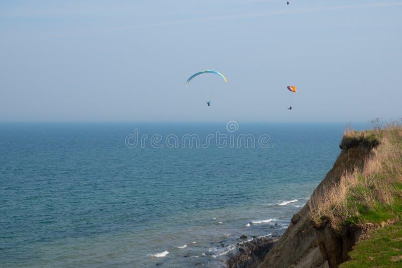 Los planeadores de Para vuelan a lo largo de la costa escarpada del mar B?ltico imágenes de archivo libres de regalías