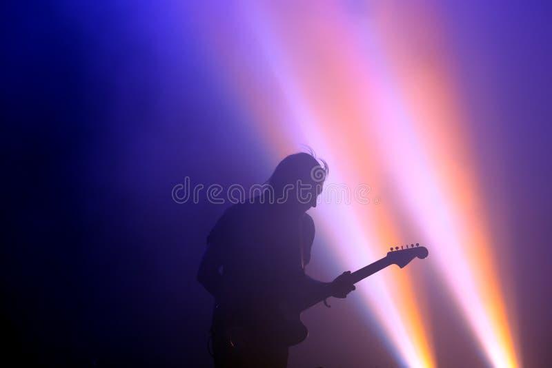 Los Planetas (西班牙带)的吉他弹奏者的剪影在音乐会的,在小谎节日 免版税图库摄影