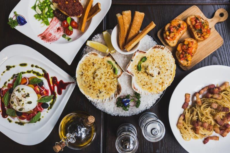 Los platos italianos en la tabla incluyendo la ensalada de Burrata, bacalao cocido con la salsa, espagueti Carbonara, cocieron co foto de archivo libre de regalías