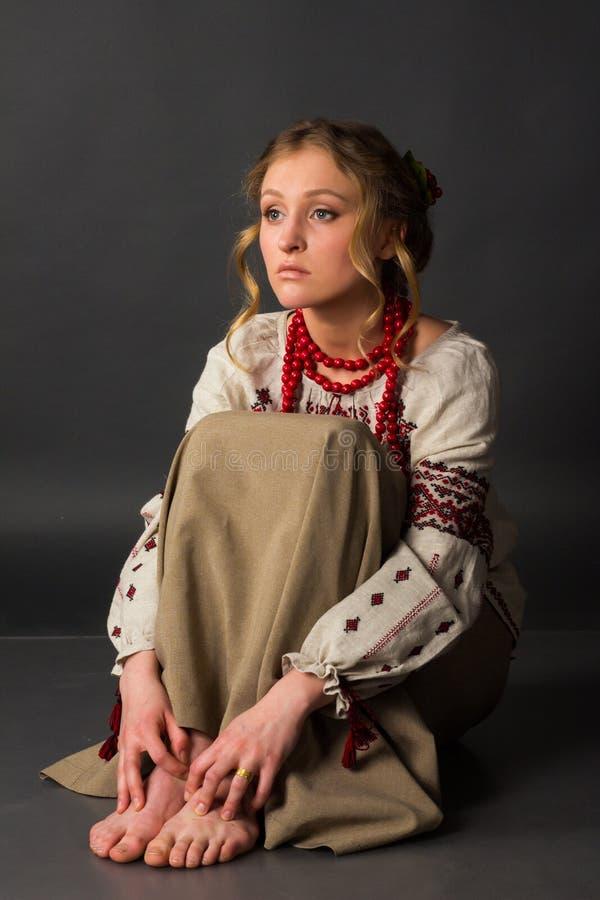 Los pobres asustaron bastante a la muchacha en el bordado ucraniano que se sentaba en el piso imágenes de archivo libres de regalías