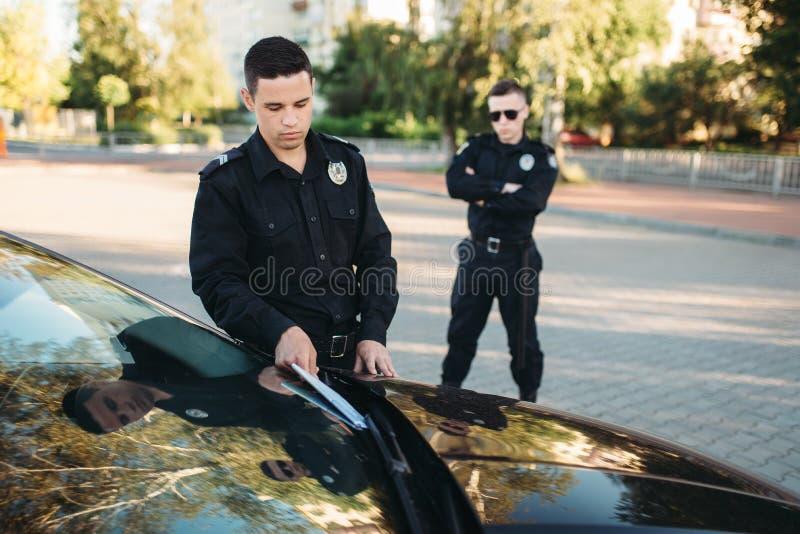 Los policías en uniforme escriben la multa del coche imagenes de archivo