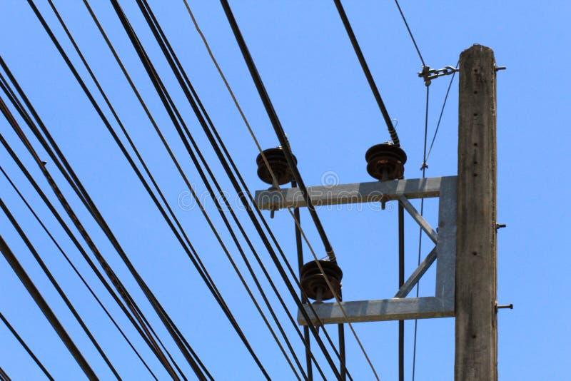 Los polos de la electricidad en la ciudad tienen cables largos en la tierra con la transmisión Para enviar al hogar imagenes de archivo