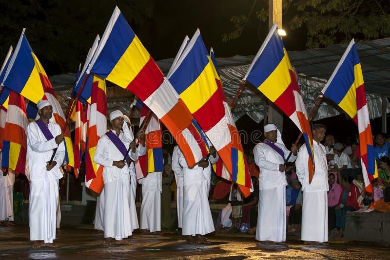 Los portadores de bandera budistas desfilan a través de las calles de Kandy durante el Esala Perahera en Sri Lanka imagen de archivo