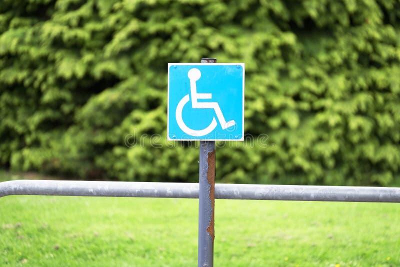 Los poseedores de una tarjeta de identificación azules inhabilitados de la silla de ruedas firman en el aparcamiento fotografía de archivo