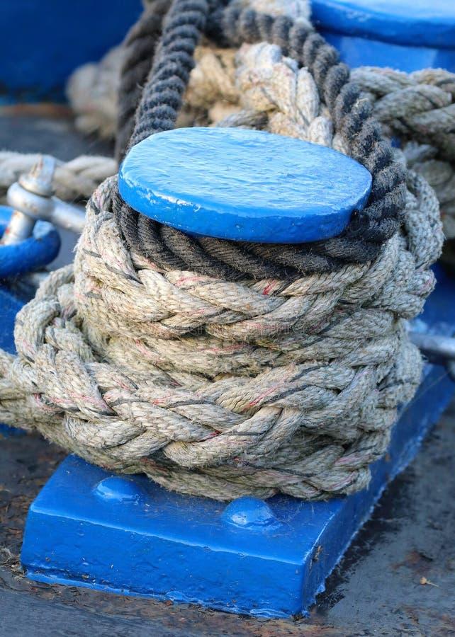 Los posts azules del amarre del barco cubiertos con la sujeción ropes fotos de archivo libres de regalías