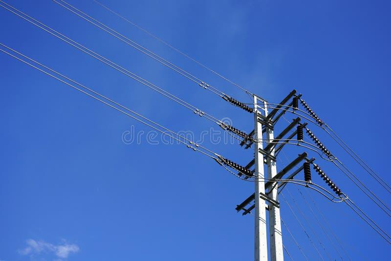 Los posts eléctricos de alto voltaje con la línea eléctrica telegrafían contra s azul foto de archivo libre de regalías