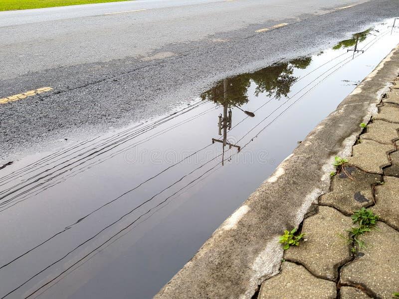 Los posts y la línea de la electricidad reflejan en el anegado en la calle foto de archivo libre de regalías