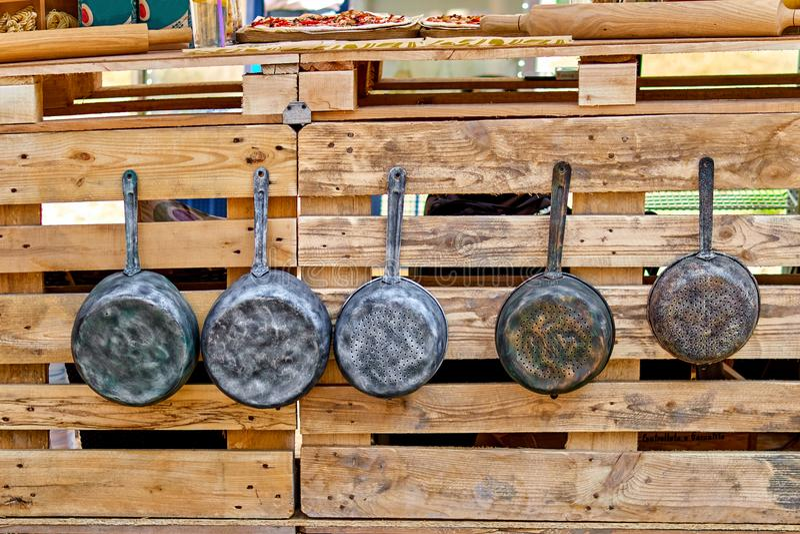 Los potes viejos del hierro y los sartenes antiguos cuelgan en los ganchos Utensilios viejos de la cocina foto de archivo