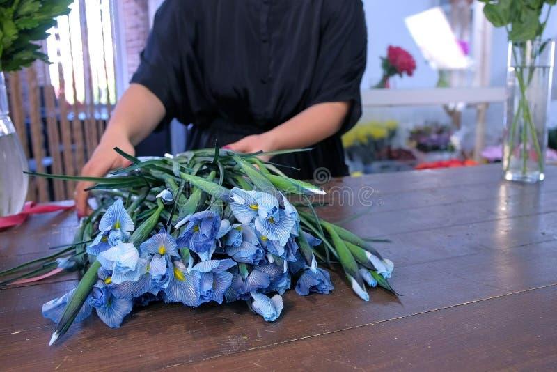 Los prapares del florista de la mujer irisan las flores para el ramo en tienda florística en la tabla de madera imágenes de archivo libres de regalías