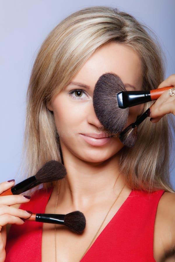 Los procedimientos de la belleza, mujer sostienen cepillos del maquillaje cerca de cara. imagen de archivo