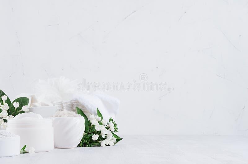 Los productos blancos delicados orgánicos de los cosméticos - crema, sal, arcilla, friegan y toalla del algodón del baño, flores  foto de archivo