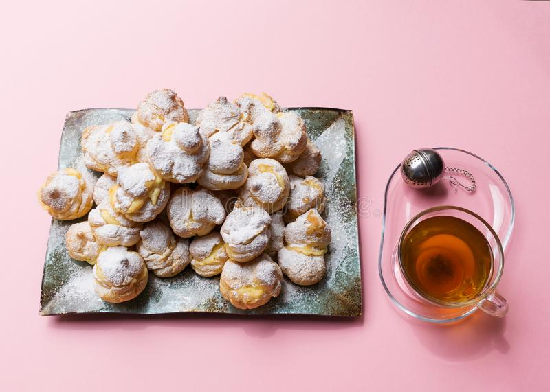 Los profiteroles hechos en casa sirvieron en una placa con una taza de té en un fondo rosado Endecha plana fotografía de archivo
