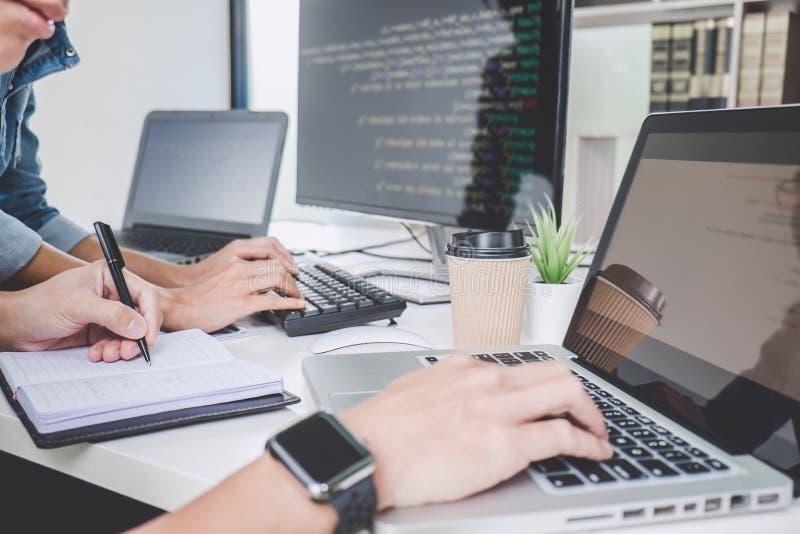 Los programadores que cooperan en la programación y la página web que se convierten que trabajan en un software desarrollan la of fotos de archivo libres de regalías