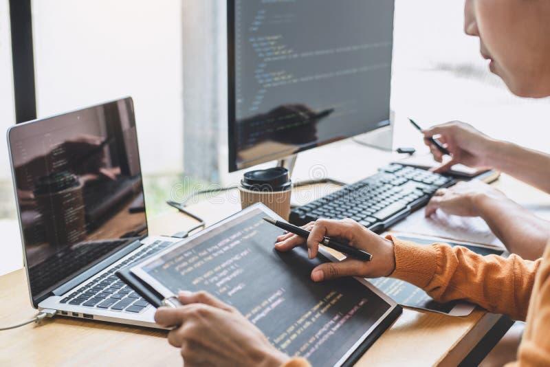 Los programadores que cooperan en la programaci?n y la p?gina web que se convierten que trabajan en un software desarrollan la of fotos de archivo