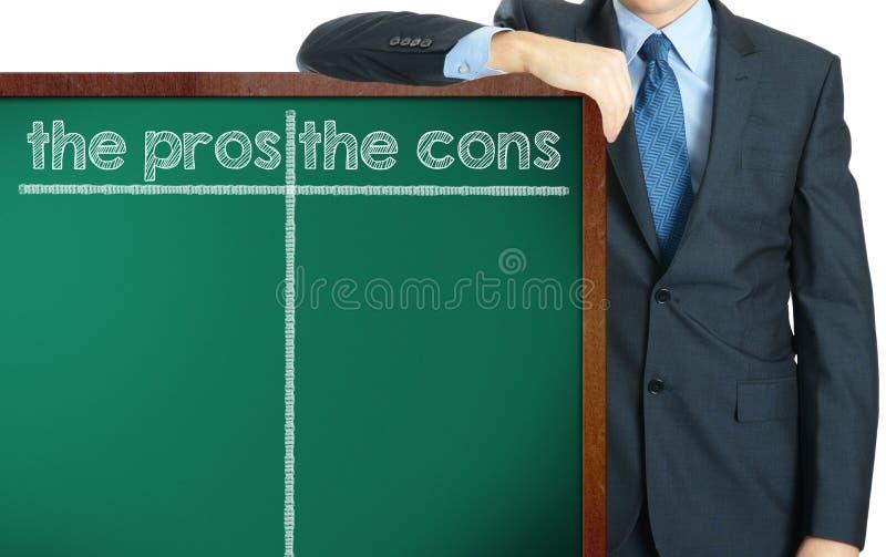 Los pros y el contra en la pizarra que presenta por el hombre de negocios o foto de archivo