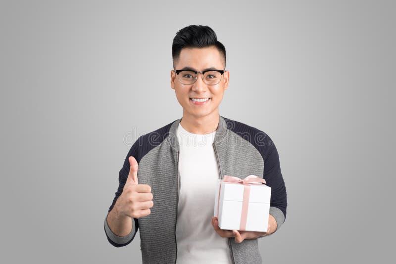 Los pulgares asiáticos del hombre suben y sosteniendo la caja de regalo Tiro del estudio, parte posterior del gris fotografía de archivo libre de regalías