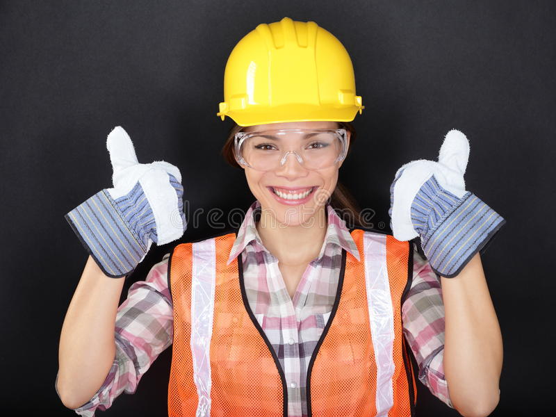 Los pulgares del trabajador de construcción suben el retrato feliz de la mujer foto de archivo