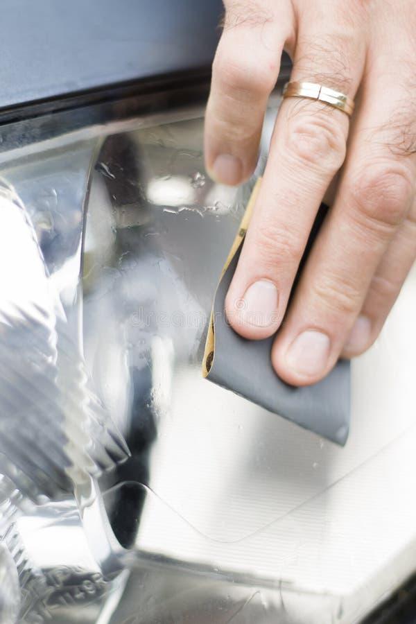 Los pulimentos de la mano del ` s del mecánico de coche con papel de lija y agua helaron el vidrio del reflector fotos de archivo