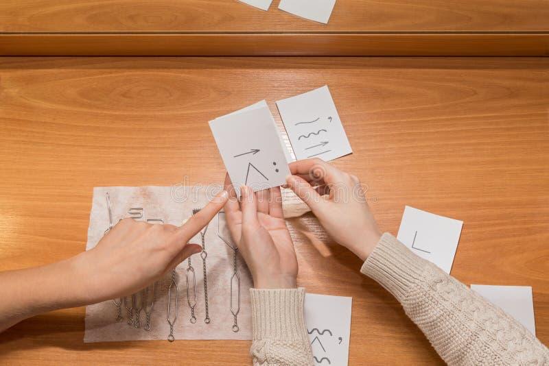 Los puntos del doctor a la tarjeta de sonido manos en las tarjetas del ejercicio de la tenencia de la tabla para los sonidos de p fotos de archivo libres de regalías