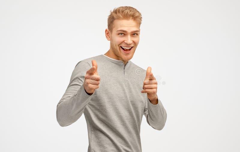Los puntos masculinos sin afeitar alegres en usted, tienen expresión feliz, cerda, expresan su opción El hombre hace gesto del ar fotografía de archivo