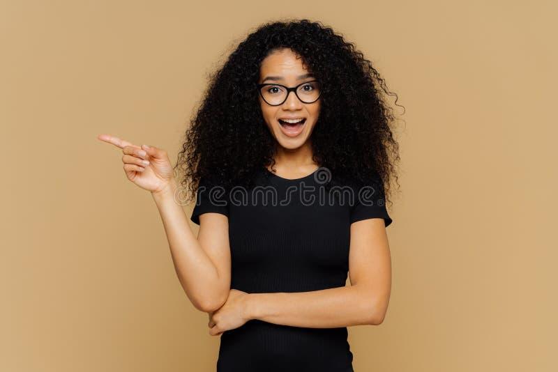 Los puntos morenos de la mujer de la raza mixta a un lado con el dedo índice, tienen expresión curiosa alegre, producto impresion fotos de archivo