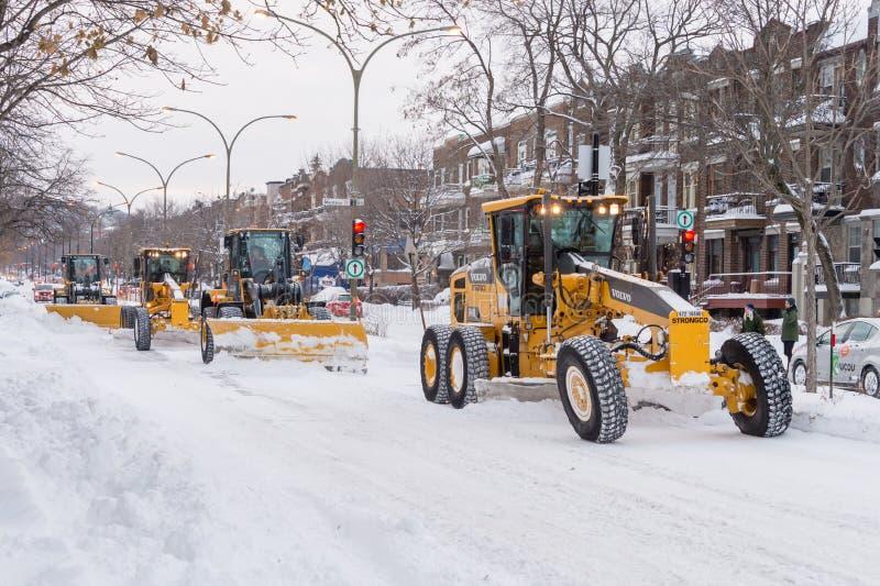 Los quitanieves están despejando nieve del camino imagenes de archivo