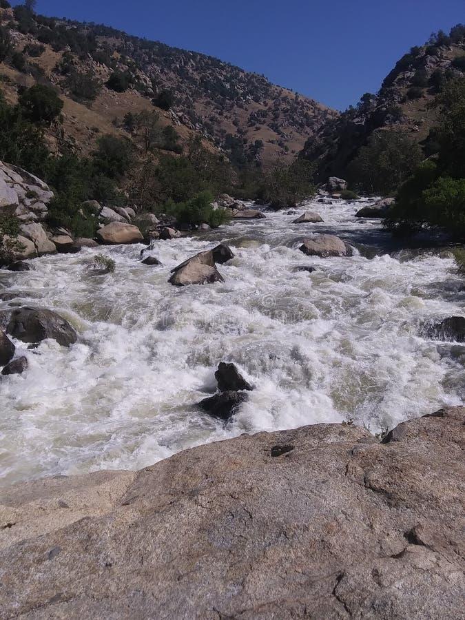 Los rápidos que rabian de un río fresco de la montaña foto de archivo
