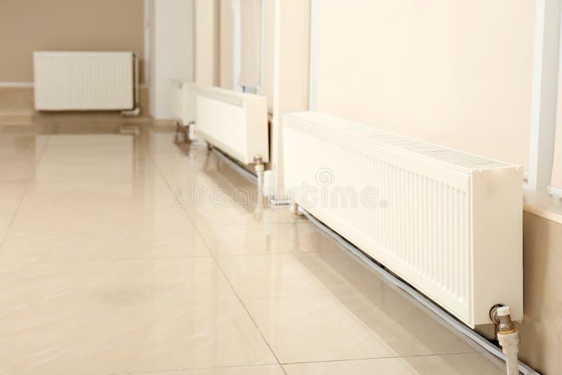 Los radiadores modernos de la calefacción acercan a ventanas cerradas foto de archivo libre de regalías