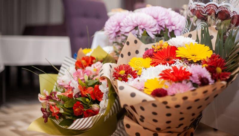 Los ramos de crisantemos coloridos, lirios rojos, los gerberas rosados envolvieron en un paquete decorativo fotos de archivo
