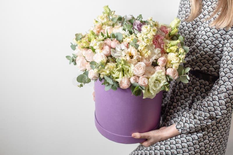 Los ramos de lujo de mezcla florecen en la caja del sombrero en las manos del ` s de la muchacha foto de archivo