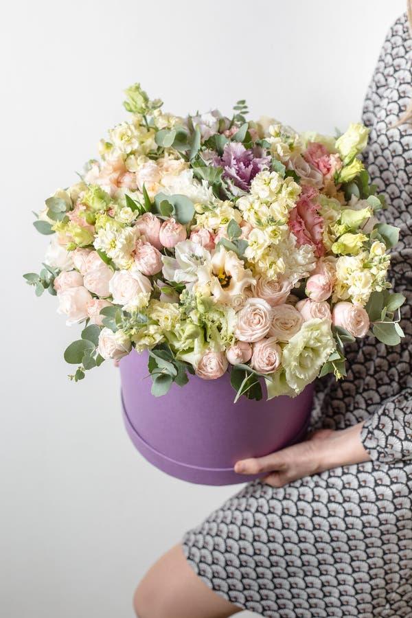 Los ramos de lujo de mezcla florecen en la caja del sombrero en las manos del ` s de la muchacha fotos de archivo libres de regalías