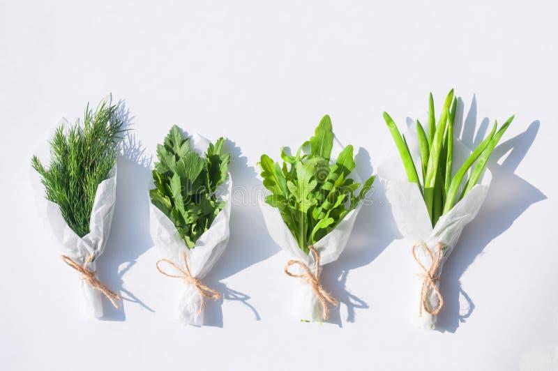 Los ramos de verdes frescos para la ensalada embalaron en el Libro Blanco en un fondo blanco aislado imagen de archivo libre de regalías