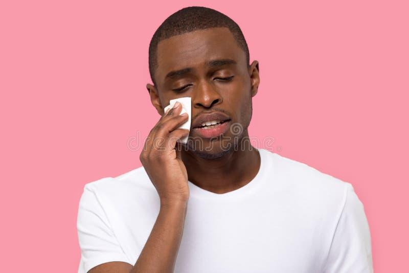 Los rasgones de barrido masculinos africanos sienten la presentaci?n infeliz sobre fondo rosado fotografía de archivo libre de regalías